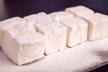 Marshmallow cubes sugar powdered lying on black plate