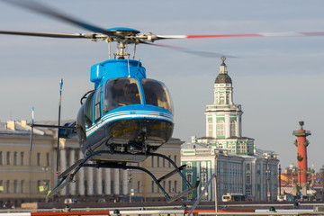 Small helicopter takes off from the helipad in Saint-Petersburg, against the backdrop of the Kunstkamera, the arrow of the Vasilyevsky Island.