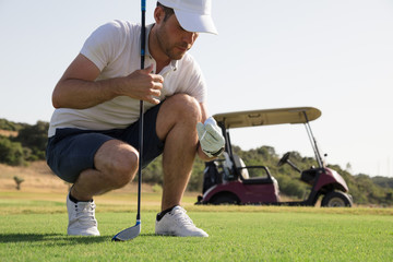 Golf player putting ball on the course before teeing off in front of golf cart