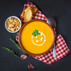 Pumpkin and carrot soup with cream and herbs on black concrete background with copy space.  Top view