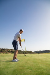 A man hitting golf ball at hole with flag