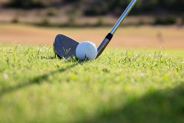 Close-up on a golf club hitting the ball