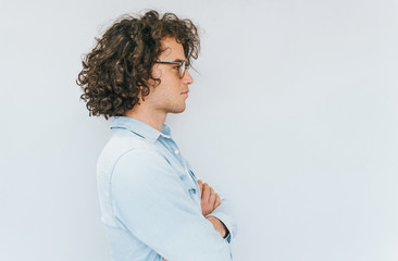 Profile view of handsome young male with curly hair, wearing denim shirt and round spectacles looking to the copy space for advertisement. People race concept.
