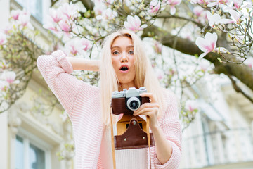 Emotional portrait of blond excited woman photographer says wow, looks bugged eyes and rounded mouth, being amazed to see something unexpected with old retro camera under blooming magnolia tree.