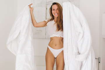 Crazy laughing girl locating on bedding. Playing with bed sheets