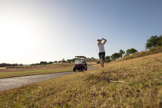 Golf player after shot near golfcart