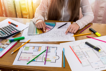 Woman designer with house plan and colour sampler