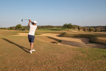Golf player swinging ball over sand bunker