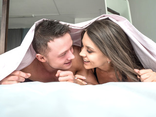 Smiling young couple lying under the coverlet in bed