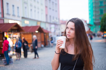 Woman with takeaway drink walk on street. Woman hold disposable coffee cup. Coffee or tea mood. Drink and food during summer vacation or travelling. Beauty girl with long hair and natural makeup