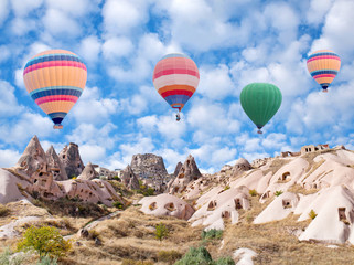Uchhisar Fortress and colorful hot air balloons flying over Pigeon Valley in Cappadocia, Turkey