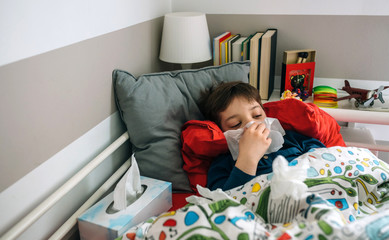 Cold child lying on the bed blowing his nose with handkerchiefs