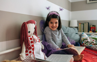 Little girl looking at camera disguised as a butterfly sitting on the bed next to her doll reading a book each