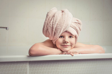 Little girl with a towel on her head in the bathroom after bathing.