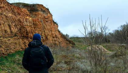 A lonely young man in a black jacket in a blue hood with a backpack on his back is in a deserted area near a limestone cliff overgrown with rare trees and shrubs.