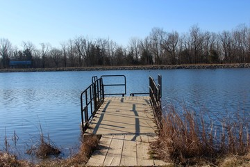 The small fishing pier on the lake and a sunny day.