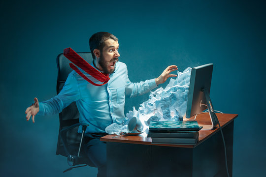 Young stressed handsome businessman working at desk in modern office shouting at laptop screen and being angry about spam