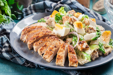 Healthy caesar salad with chicken, eggs and croutons