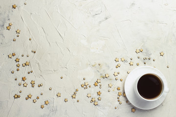 Cup of coffee and stars on a light stone background. Flat lay, top view