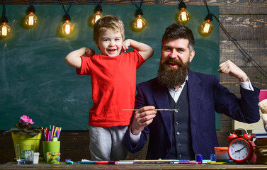 Fatherhood concept. Talented artist spend time with son. Child cheerful and teacher painting, drawing. Teacher with beard, father and little son having fun in classroom, chalkboard on background.