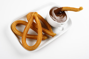 churros with chocolate on a white tray