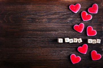 Heart shaped chewing candies and words I love you on cubes, wooden background. Free space for your text.