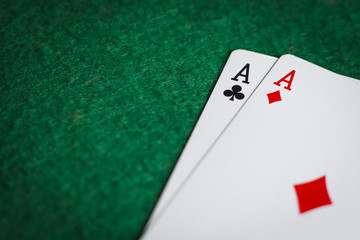 A pair of aces on a green poker table