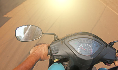 The man's hand and the speedometer of the scooter are close-up.