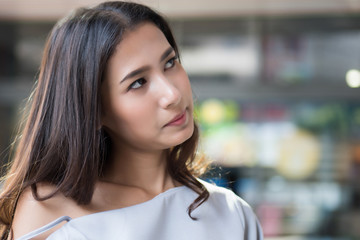upset girl frustration; unhappy angry woman portrait with frustrated, bored, disgusted face; negative unhappy upset angry asian woman looking up outdoor city environment; asian woman young adult model