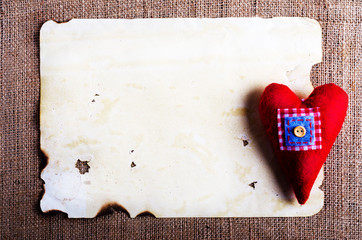 Old vintage sheet of paper and red textile heart on burlap, sackcloth background. Retro design effects.