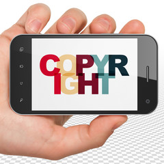Law concept: Hand Holding Smartphone with Painted multicolor text Copyright on display, 3D rendering