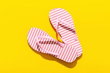 Pink Beach flip flop on yellow background