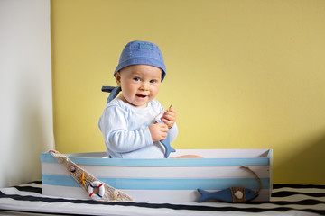 Cute toddler boy, sitting in a big wooden boat at home, playing with wooden fishes