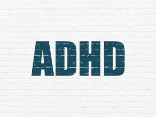 Healthcare concept: Painted blue text ADHD on White Brick wall background