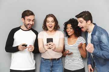 Shocked happy group of friends using mobile phones looking aside.