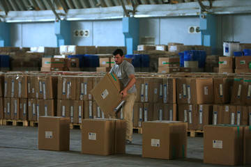 A worker of Iraqi Independent High Electoral Commission carries a box at a warehouse in Najaf