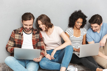 Happy group of friends using laptop computers.
