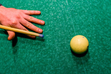 Player arm with the cue and ball on the green cloth. Russian billiard. Top view