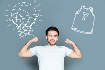 Basketball player. Cheerful hardworking sportsmen enjoying his progress in playing basketball and showing his muscles