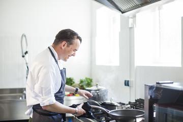 Cook preparing food in kitchen