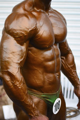 PUNE, MAHARASHTRA, INDIA, 29th March 2018, Young bodybuilder showing chest and biceps muscles in side pose, Indian Body Builders Association show, Balewadi, Baner