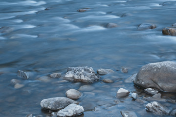 Long exposure photo of a smooth water surface on small mountain river with rocks. Beautiful natural background.