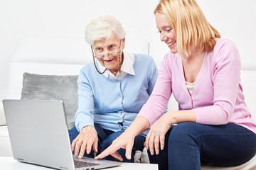 Junge Frau zeigt Seniorin am Laptop das Internet