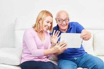 Frau und Senior mit Laptop bei einem Video Chat