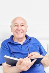 Glücklicher Senior als Rentner liest ein Buch