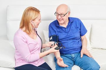 Frau macht Blutdruckmessung bei einem Senior