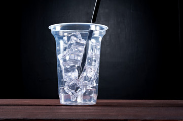 Plastic transparent cup of ice drink with straw isolated on black background. Drink - to go, take away, take out.