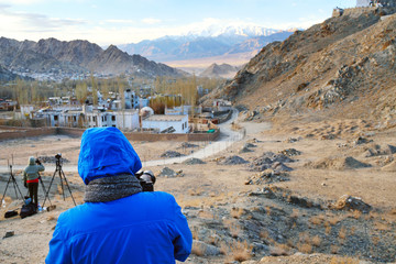 group of photographer taking landscape photo of village and snow on mountain