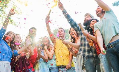 Happy friends having party,throwing confetti and using smoke bombs colors outdoor