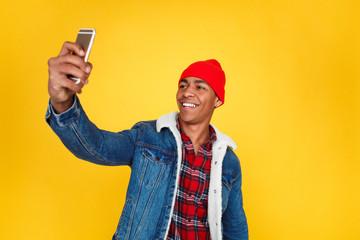 Stylish guy taking selfie on yellow